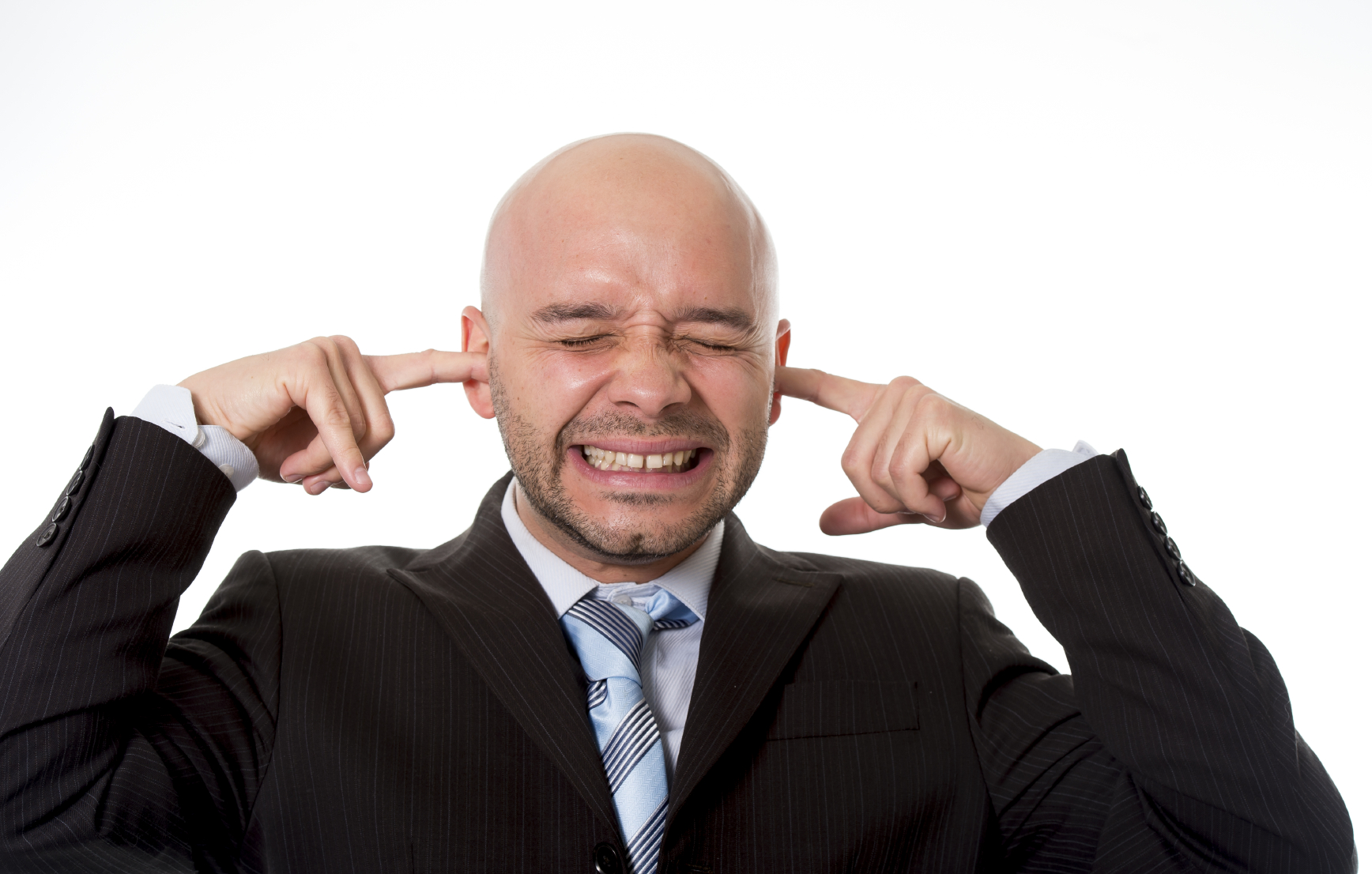 Hispanic or Brazilian businessman wearing suit and tie in stress covering his ears with fingers hoping for noise to stop and relax to come isolated on white background